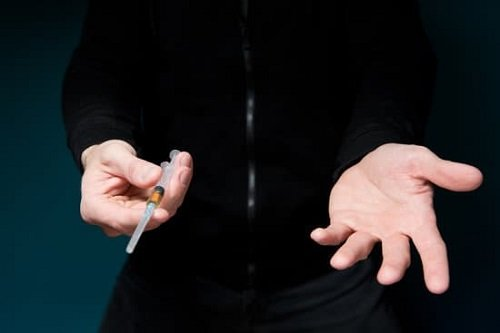 offers a syringe with heroin and requires payment, holding out his hand
